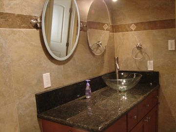 Large vanity with vessel sink and twin mirrors.
