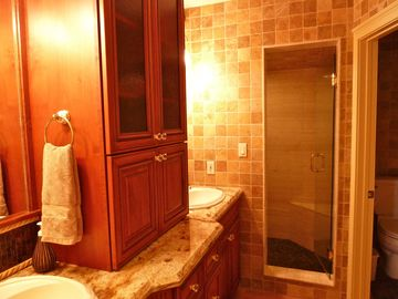 Glamorous master bathroom has double sinks, makeup station, and walk in shower.