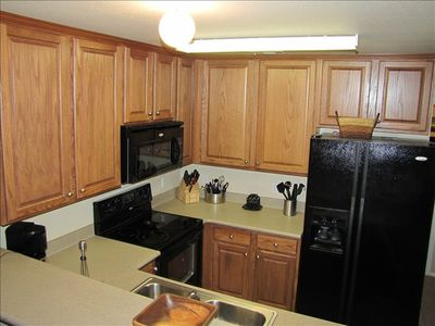 Well equipped kitchen with extra large fridge and cabinets for storage.