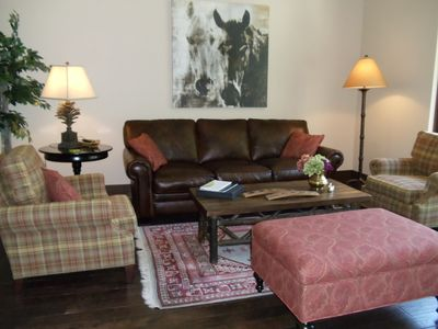 Living room with leather couch and comfortable chairs facing gas fireplace & TV.