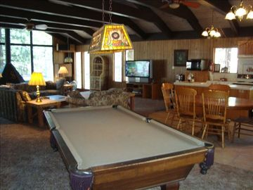 "Pool table with 50"" TV in background."