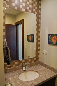 Guest bath off of entrance hall is spacious.
