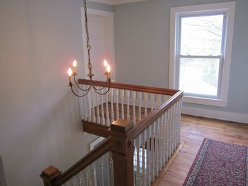 Top of stairway with beautiful chandelier.