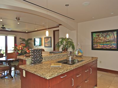 The spacious kitchen has granite countertops and travertine floors.