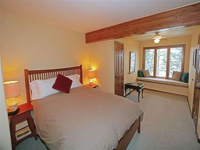 Upstairs queen bedroom with window seat facing the lake