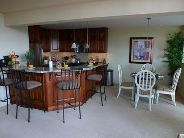 Open Granite Kitchen with GE Profile Appliances and Dining Room.