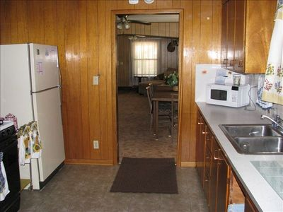 Kitchen with refrigerator, gas stove, small microwave off of the dining area