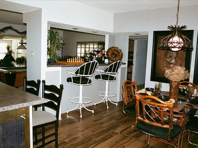 Dinning area with bar overlooking pool table and living room.