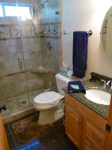 Remodeled w/shower featuring dual shower heads and floor to ceiling tile & glass