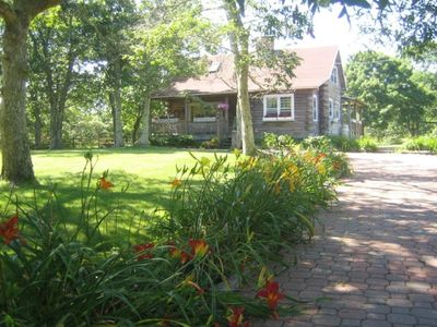 Log Cabin Home and day lilies line red brick driveway