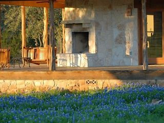 Mason lodge photo - Outside fireplace with bluebonnets in April.