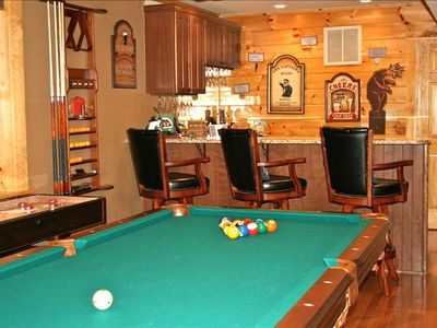 Pool table in game room with shuffleboard table to left and wet bar.