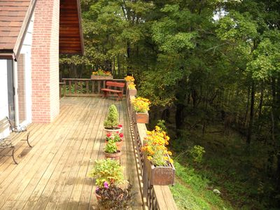 Mature woods surround the expansive deck, offering views and privacy.