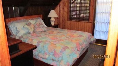One of the two upstairs bedrooms with walk out deck above front yard/forest