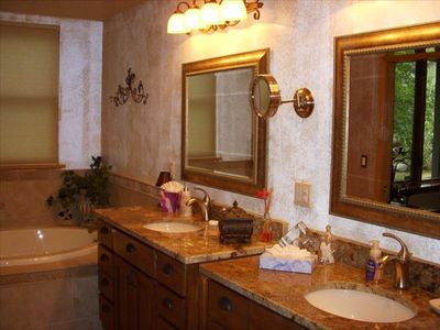 Elegant Master Bath features dual vanity with granite and jacuzzi tub.