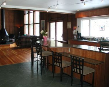 Large kitchen with huge granite island opens to living area.