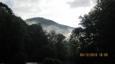 Enjoy an early morning on the balcony with amazing scenery and rushing creek.