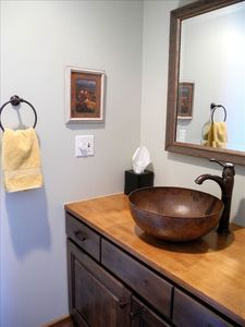 Half bath vanity with copper bowl sink.