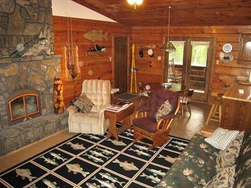 Beautiful stone fireplace in main great room, dining area and doors to porch.