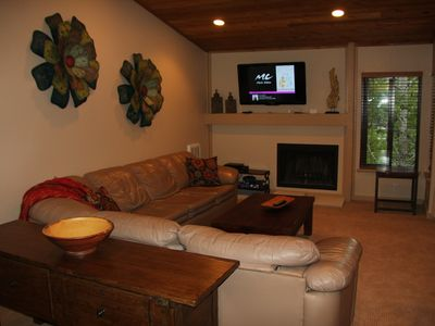 Living Room with flat screen TV, fireplace with gas starter and couch w/ sofabed