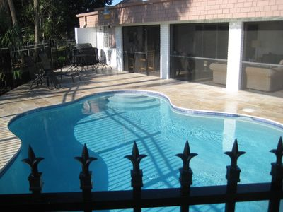 Pool with barbecue grill, lounge chairs and wrought iron table and chairs