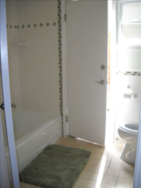 Bathroom with bathtub/shower. Door open to the backyard.