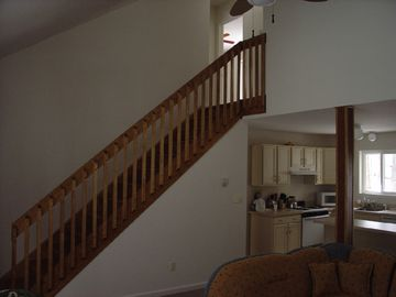 Staircase to 2nd floor & partial view of kitchen