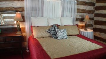 1800's Log Cabin bedroom downstairs. King bed. Call toll free 800-997-1124.