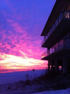 Sunset on the beach looking west through balconies. Glass balconies