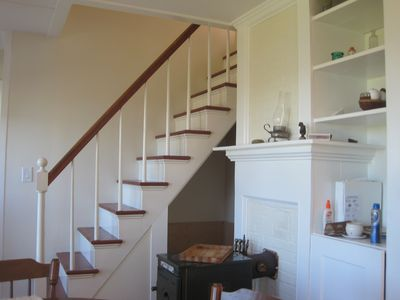 Stairs from dining room to upper floor. Wood stove visible, bottom center.