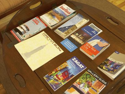 living room table with various NYC travel guides