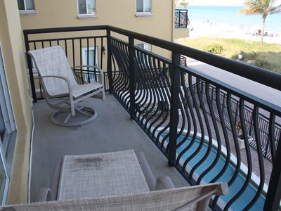 New lounge chair and rocking chair overlook pool and beach directly