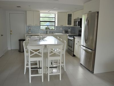 Eat in kitchen with white quartz countertops and stainless steel appliances.