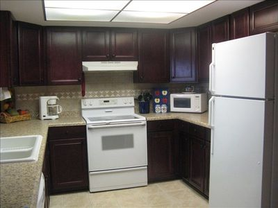 Stocked kitchen w/ flattop stove, microwave, sink, dishwasher & refrigerator.