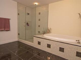 Cocoa Beach condo photo - Master bathroom has marble floors, oval jetted tub, and seamless glass shower!