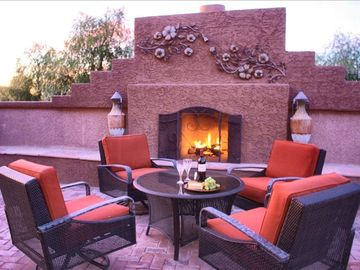 Sit beside the outdoor fireplace on cooler evenings while the chef cooks.