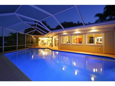Pool Area - heated pool, outdoor dining area, screened lanai, BBQ, pool light.