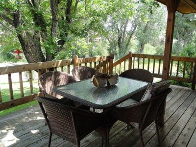 Deck of main home offers outdoor dining among mature trees and scenery!