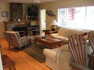 View of living room, w/master entry in background.  note wood stove/TV/stereo.