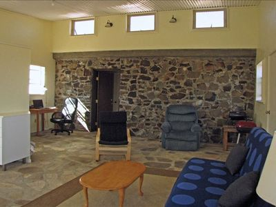 Living room.  Stone wall to the bedroom and awning windows for passive cooling.