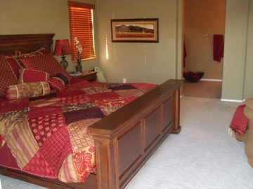 Oversized master bedroom with kng-size bed and chaise lounge and patio doors.