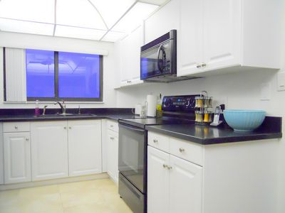 Clean, bright kitchen with solid surface counters and harbor-view window.