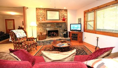 Cozy sofa, stone woodburning fireplace, cable tv overlooking deck and woods