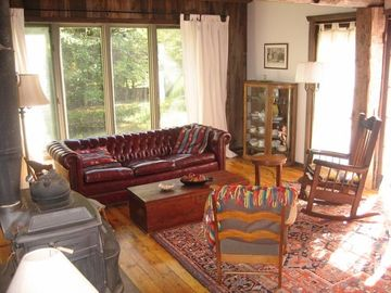 Large living room with a wood stove and french doors that open onto a deck