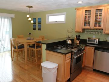 Eat in kitchen leading to back deck with outdoor seating and gas grill