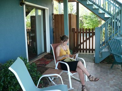 Guest enjoys the front patio. Background gate leads to the swimming pool.