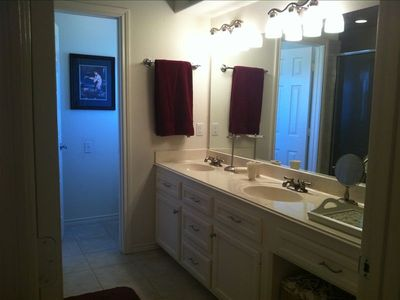 Master bath with two sinks and a vanity area