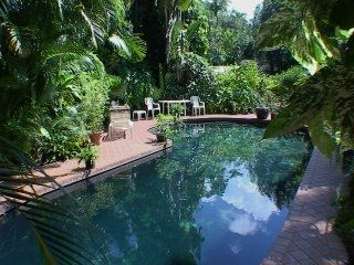 Large pool and garden with orchids and exotic birds
