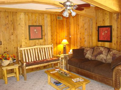 The living room offers comfortable seating, HDTV, an a wood burning stove.