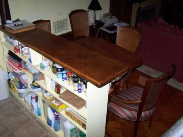 Looking northwest: kitchenette backside of bar w/ condiments, napkins, mats, etc